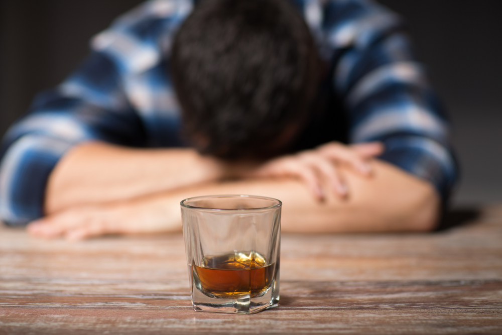 A guy with the head down in the table while having a glass of alcohol in from
